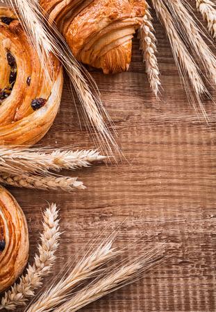 oaken: Golden wheat ears raisin rolls croissant on oaken wooden board f