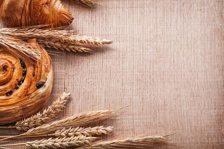 woo: Golden wheat ears sweet croissant roll with raisins on oaken woo