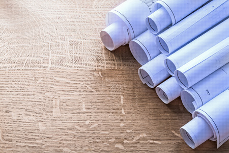 oaken: Heap of blueprint rolls on wooden oaken board construction conce