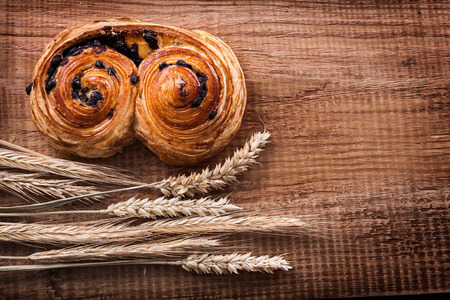 Newly-baked raisin roll bunch of wheat ears on oak wooden board Stock Photo