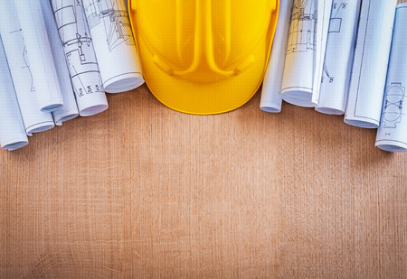 construction plan: Oaken wooden board with building helmet and blueprints construct