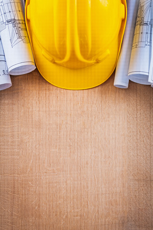 yellow hard hat: Oaken wooden board with yellow hard hat and blueprints construct