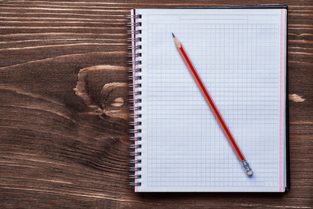 squared: Pencil and squared notepad on pine brown wooden board office con