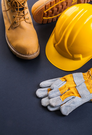 protective wear: protective wear construction helmet work gloves working boots on black background