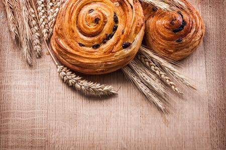 oaken: Ripe wheat ears raisin baked rolls on oaken wooden board food an