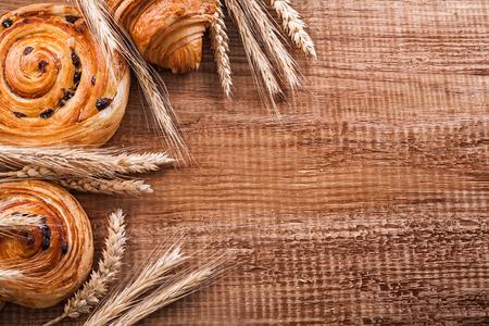 oaken: Ripe wheat ears raisin buns croissant on oaken wooden board food
