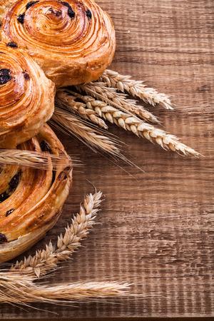 oaken: Ripe wheat ears rich rolls with raisins on oaken wooden board fo