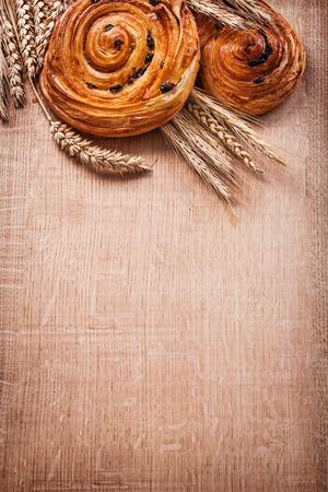 oaken: Ripe wheat ears rich raisin baked rolls on oaken wooden board fo