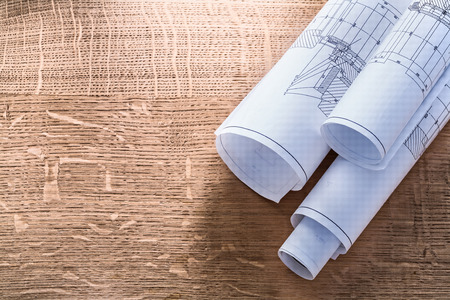 house blueprint: Rolls of blueprints on wooden oaken board construction concept Stock Photo