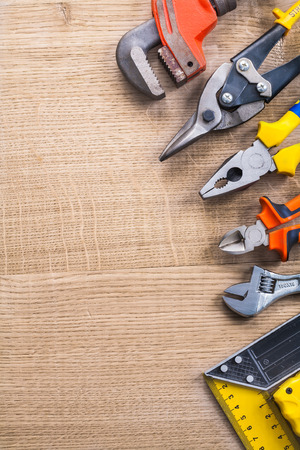 wirecutters: spanner cutter pliers nippers square ruler on wooden board with Stock Photo