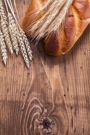 processed grains: to baguettes and ears of wheat rye on vintage wooden board with Stock Photo
