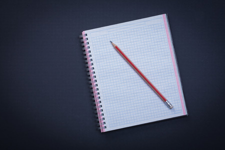 copybook: White checked copybook with red pencil on black background educa