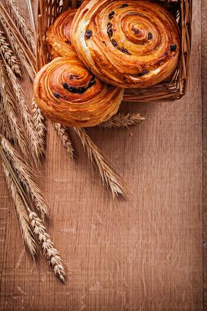 oaken: Wicker basket with raisin pastry wheat ears on oaken wooden boar Stock Photo