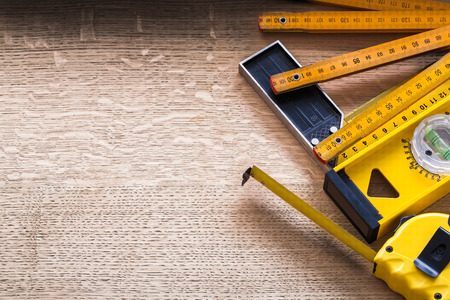 square ruler: Wooden meter tape measure construction level and square ruler on Stock Photo