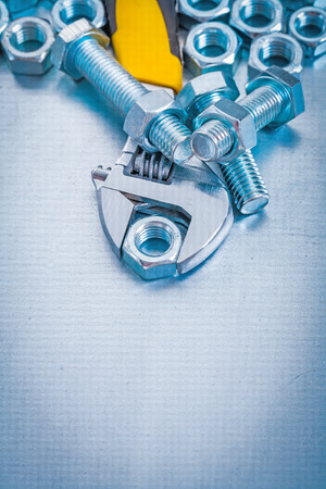 screw key: Adjustable key metal bolt details and screw nuts on metallic bac