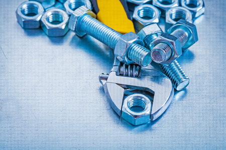 screw key: Adjustable key threaded bolt details and screw nuts on metallic Stock Photo