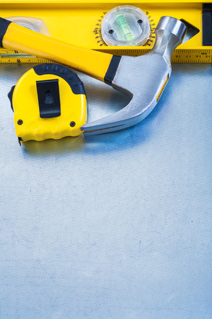 tape line: Construction level tape line claw hammer on metallic background Stock Photo