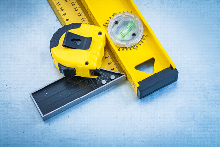 square ruler: Tape line construction level and square ruler on metallic background