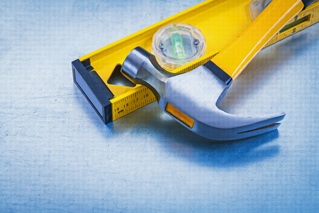 claw hammer: Yellow construction level and claw hammer on metallic background