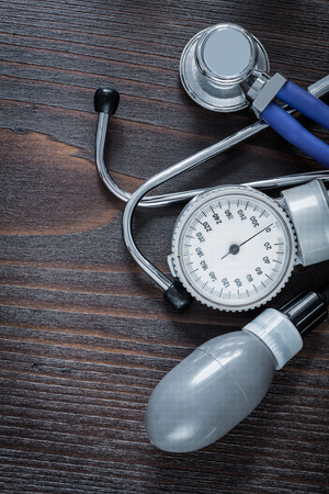 blood pressure monitor: Medical stethoscope and blood pressure monitor on vintage wooden Stock Photo