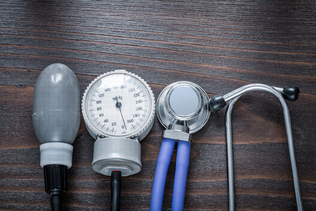 tonometer: Medical stethoscope and tonometer on vintage wooden background m