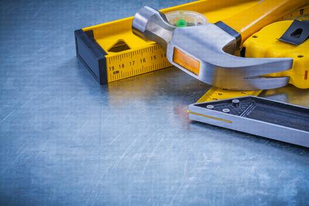 メタリックな背景メンテナンス コンセプトに爪ハンマー巻尺建設レベル正方形の定規の水平方向のバージョン。
