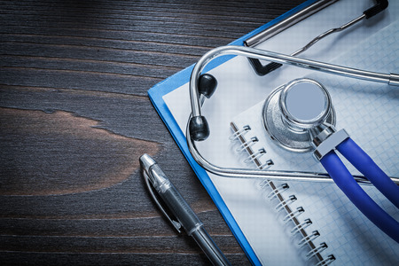 squared: Clip board squared notepad pen and medical stethoscope tablet on vintage wooden background medicine concept