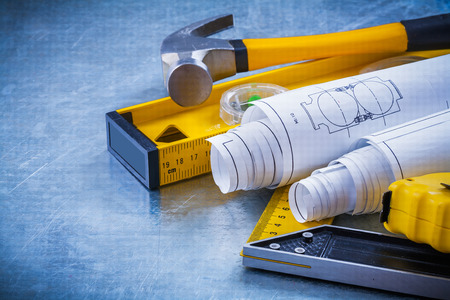 square ruler: Close up image of hammer measuring line construction plans and level square ruler on metallic background maintenance concept.