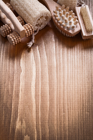 scrubbing: Scrubbing brush loofah and peeling massagers on pine vintage wood board sauna concept