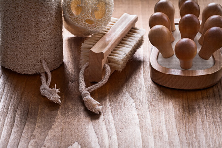 scrubbing: Scrubbing brush loofahs and back massager on pine vintage wood board healthcare concept Stock Photo