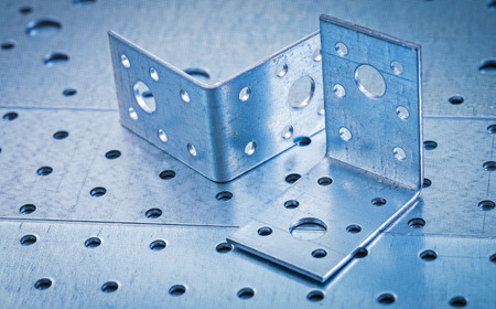 drilled: Stainless drilled angle bars on perforated metallic background construction concept. Stock Photo