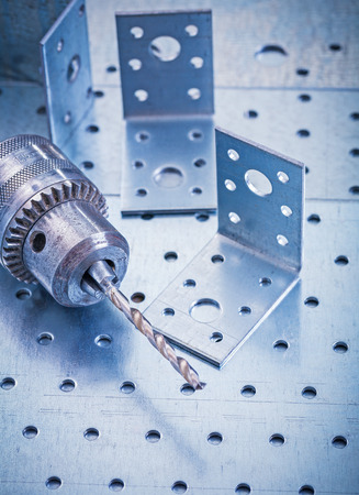 drilled: Stainless drilled angle fasteners and metal drill on perforated metallic sheet construction concept. Stock Photo