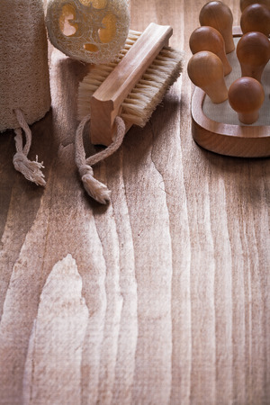 massager: Vertical image of bath brush loofahs and back massager on pine vintage wood board healthcare concept Stock Photo
