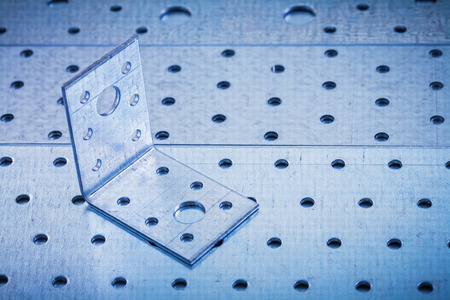 angle bar: Drilled angle bar on perforated metallic texture construction concept. Stock Photo