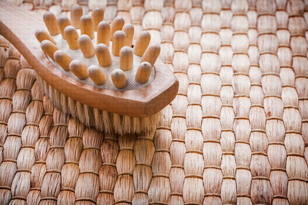 scrubbing: Horizontal image of wooden massager with scrubbing brush on wicker background healthcare concept