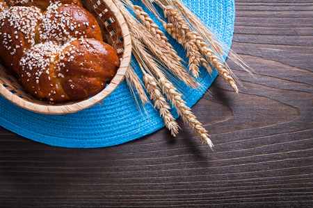 long loaf: Long loaf in wicker basket wheat rye ears with wattled cloth on wooden vintage board food and drink concept.