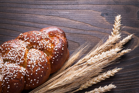 long loaf: Long loaf wheat rye ears on wooden background food and drink concept.