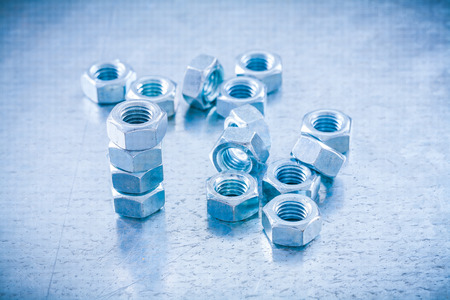 threaded: Metal threaded screw nuts on metallic background construction concept.