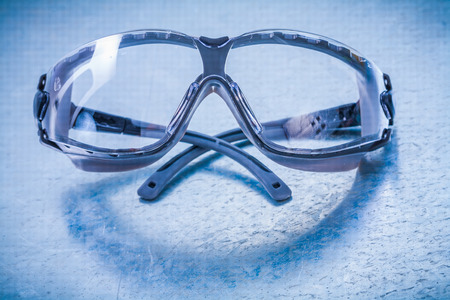 protective eyewear: Plastic protective eyewear on metallic background construction concept. Stock Photo