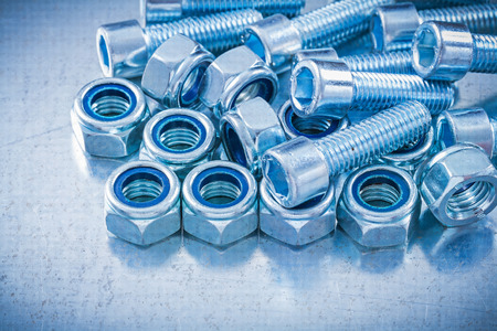 threaded: Heap of threaded construction nuts and screw bolts on metallic background maintenance concept.