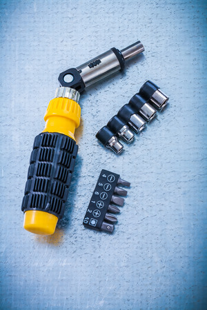 turnscrew: Reversible turnscrew screwdriver bits and torxes on metallic background construction concept. Stock Photo