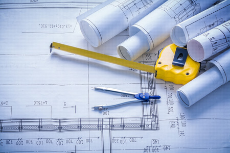 tapeline: rolled blueprints compass and yellow tapeline. Stock Photo