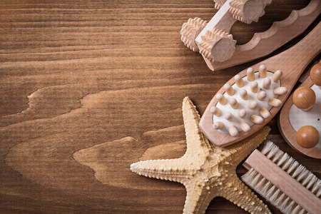 scrubbing: Set of massagers starfish and scrubbing brush on pine vintage board healthcare concept Stock Photo