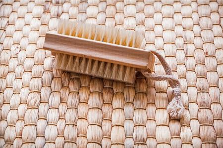 scrubbing: Single wooden scrubbing bath brush on wicker mat healthcare concept