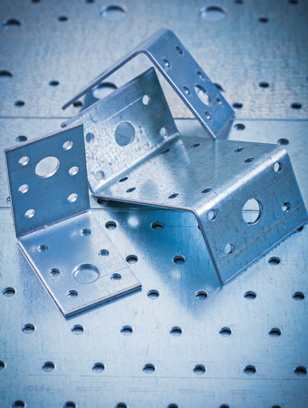 fasteners: Stainless drilled angle fasteners on perforated metallic sheet construction concept.
