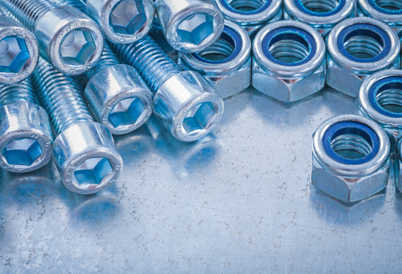 threaded: Threaded stainless screw bolts and nuts on metallic background construction concept.