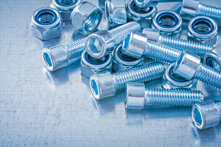 threaded: Variation of threaded screw nuts and bolt details on metallic background construction concept.