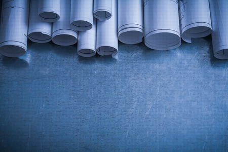 Rolled white blueprints on scratched metallic surface copy space image construction concept.