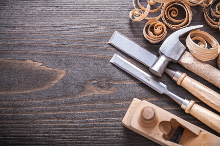 Planer claw hammer metal firmer chisels and wooden curled shavings on vintage wood board construction concept.