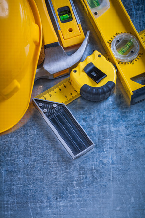 toolset: Try square construction level tape-measure protective helmet and claw hammer on metallic background vertical version maintenance concept.